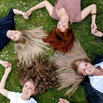 4 happy girls with beautiful hair laying on grass holding hands