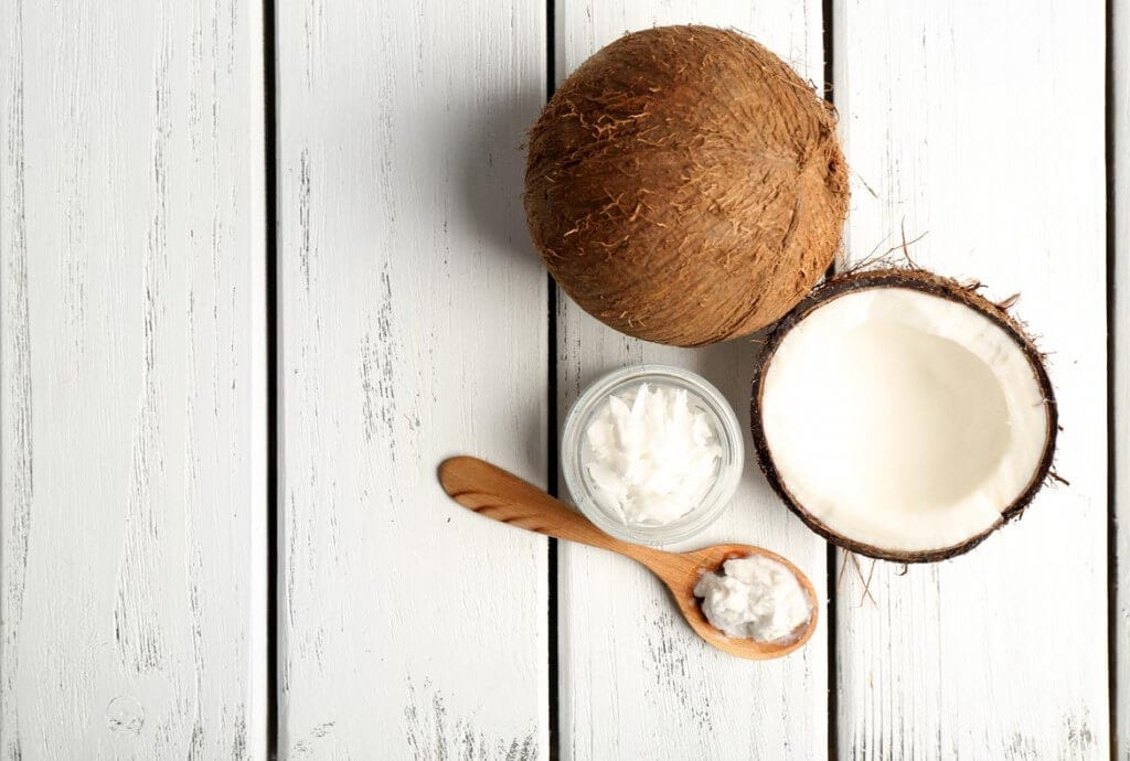 halved coconut with coconut oil in a spoon