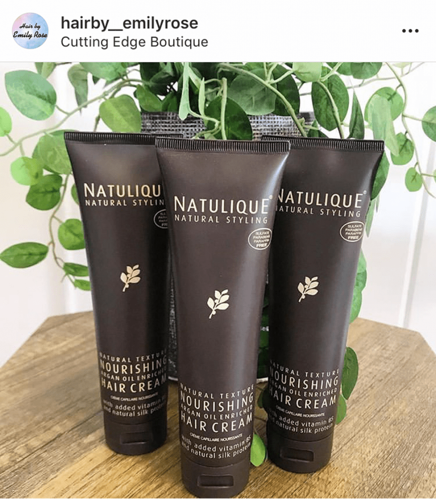 NATULIQUE hair product bottles on a table in front of plant