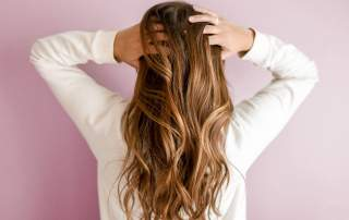 Brown hair hold wavy hairstyle with hands in hair on pink background